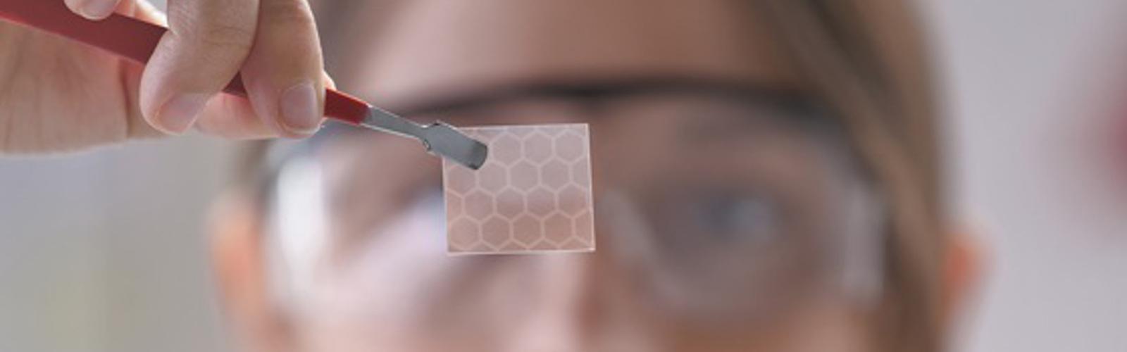 Zu sehen ist im Hintergrund eine Frau, die mit einer Pinzette eine Materialprobe hochhält
